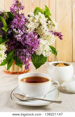 Cup of tea and branch of lilac flower in wicker basket on linen tablecloth. Spring tea time concept. Breakfast tea cup.