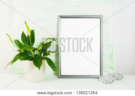 Silver frame mockup with flower pot and candles. Portrait or poster white frame mockup. Empty white frame mockup for presentation artwork design.