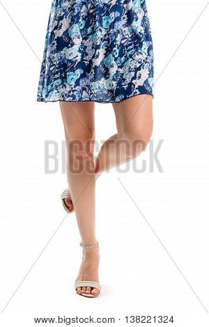 Girl's legs in heels. Summer shoes and floral garment. Short blue dress with print. Light apparel and footwear.