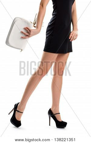 Woman's legs in black heels. Short black dress and purse. Attractive evening apparel. Luxury shoes from spring collection.