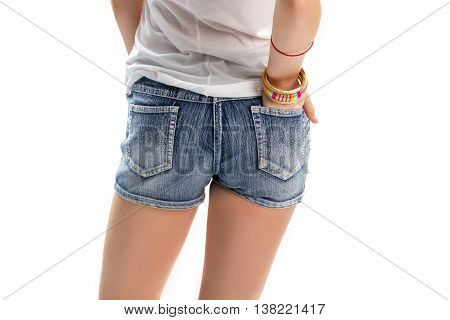 Girl in short denim shorts. Hand in back pocket. Jeans shorts from new collection. Casual clothes with simple accessories.
