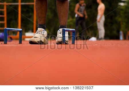 White shoes with mans legs standing on orange athletic running surface between two florr mounted blue handles, blurry people training background.