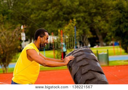 Man wearing yellow shirt and blue shorts lifting large tractor tire during strength excercise, outdoors training facility with orange athletic surface, green trees background.