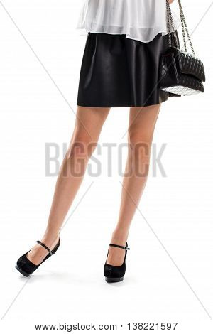 Woman in short skirt. Black skirt and bag. Quilted leather purse and footwear. Handbag from new collection.