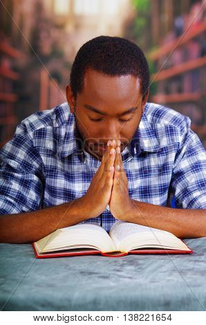 Religious man sitting while praying and reading from open book on desk in front, religion concept.