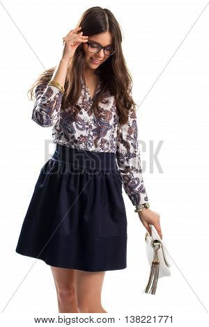 Woman smiling and touching glasses. Dark skirt and floral shirt. Precious bracelets and classic watch. Model wears new apparel.