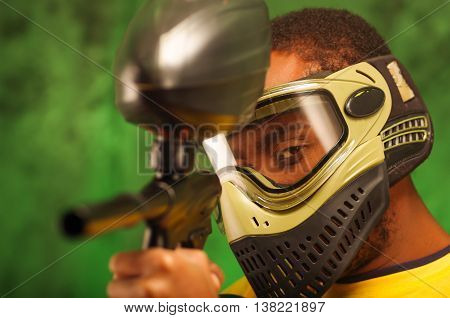 Closeup headshot man wearing green and black protection facial mask facing camera pointing paintball gun.