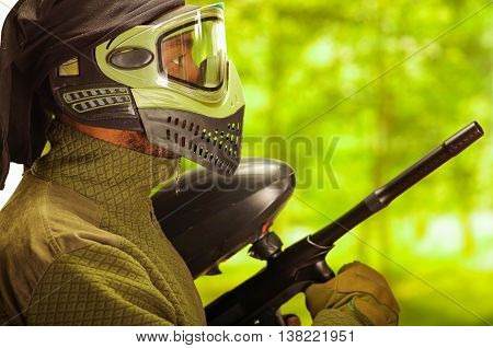 Closeup headshot man wearing jacket, green and black protection facial mask standing in profile angle with weapon, forest background, paintball concept.