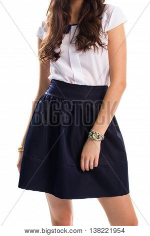 Girl in navy skirt. White blouse with short sleeves. College outfit for spring. Small classic watch with strap.