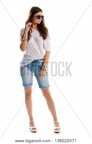 Woman in long denim shorts. White tunic and sunglasses. Summer apparel with accessories. New wedge shoes.