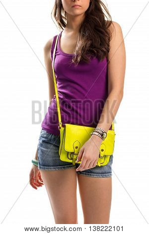 Woman in purple tank top. Handbag and short shorts. Simple and fashionable clothing. Summer outfit with colorful accessory.