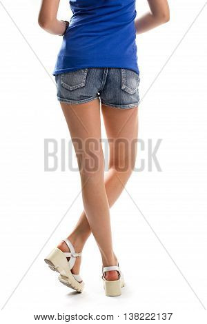 Woman's legs in white sandals. Blue top and shorts. Trendy summer shoes. Stay true to your style.