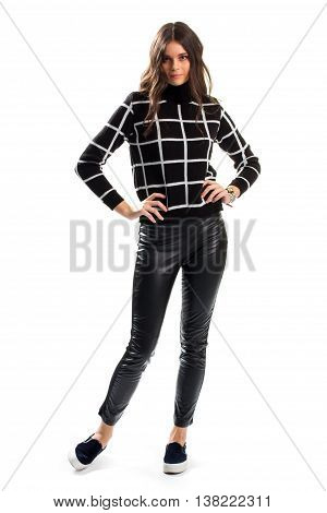 Lady in black checkered sweater. Skinny pants and footwear. Dark autumn outfit. Stylish design of new garment.