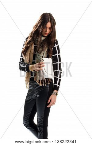 Woman touches white clutch bag. Beige scarf and black pants. Autumn look with stylish accessories. Brand new purse.