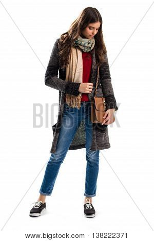 Girl in striped sweater coat. Brown bag and blue jeans. Trendy outerwear and accessory. Leather handbag of top quality.