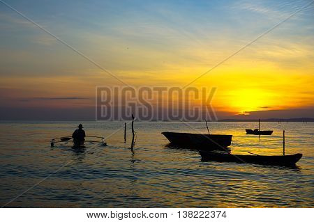 Silhouette of a traditional fisherman on boat during beautiful sunrise at Labuan island,Malaysia.