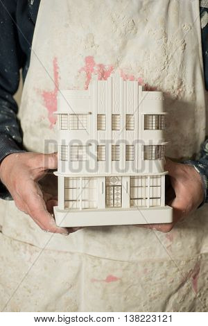 Scale Model Of Architectural Building Held By Two Hands