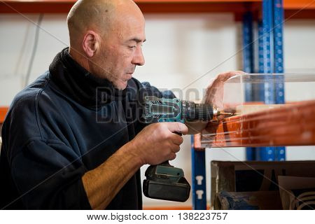 Man Drilling Holes On A Side Of Clear Acrylic Frame