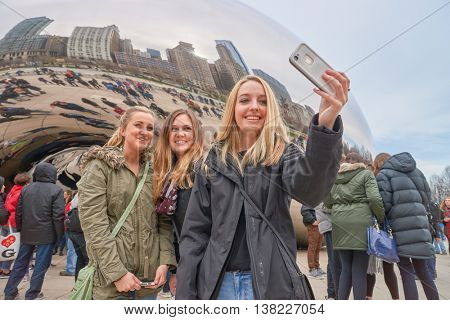 CHICAGO, IL - CIRCA MARCH, 2016: woman taking a selfie near Cloud Gate. Cloud Gate is a public sculpture by Indian-born British artist Anish Kapoor.