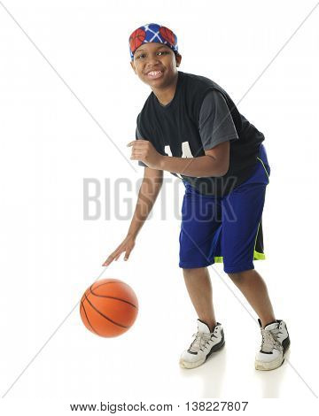 A preteen boy looking at the viewer as he happily dribbles his basketball.  On a white background.