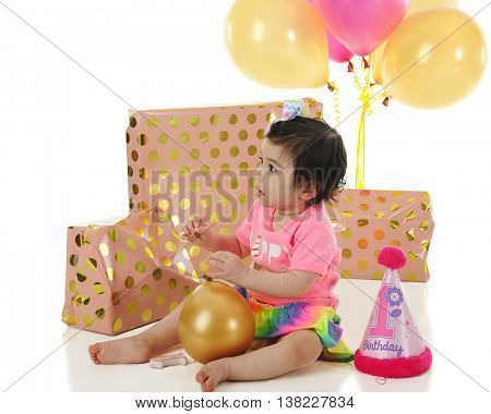 An adorable one-year-old  sitting among her wrapped gifts and balloons on her birthday.  On a white background.