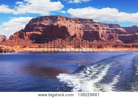 Foamy trace of motorboat crosses the emerald waters. Red sandstone hills surround the lake. Lake Powell on the Colorado River