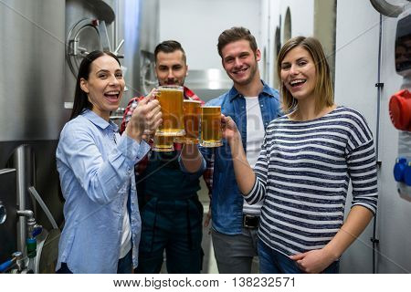 Portrait of happy brewers toasting beers at brewery