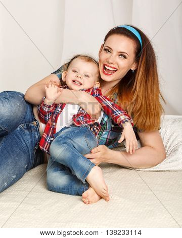 Mother and daughter at home. Young mother and baby daughter hugging. Girls dressed in plaid shirt. Daughter barefoot. Laughter and smiles. Family time