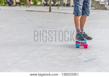 close up of boy's feet standing on modern short cruiser skateboard on asphalt background