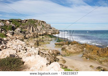 Rugged limestone cliffs and rocky beach under a blue sky with clouds at Penguin Island in Rockingham, Western Australia.