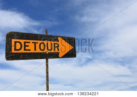 Bold orange arrow on detour sign with wispy clouds in summer sky.