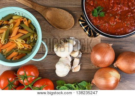 Italian meal ingredients on a wood kitchen table. A pot of sauce, colander of rigatoni, tomatoes, garlic, oregano, and onions seen from a high angle.