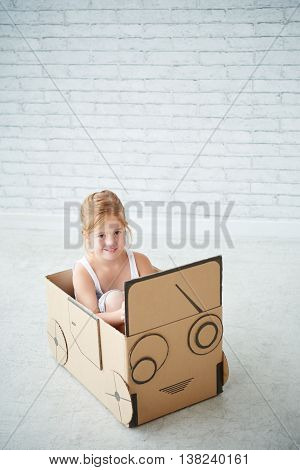Portrait of smiling girl playing with cardboard car