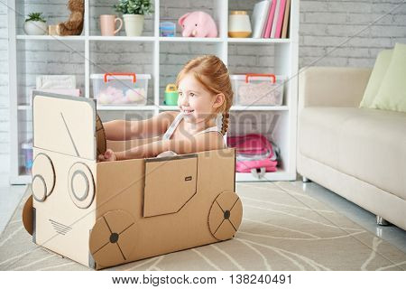 Girl playing with car made of cardboard box