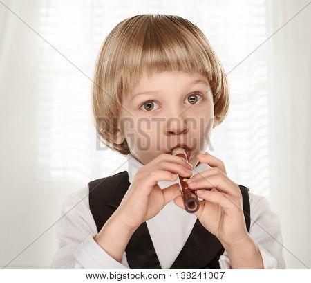 Cute little boy playing wood fife. Preschooler. on light window background