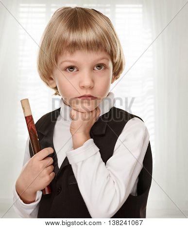 Cute little boy with wood fife. Preschooler. on light window background