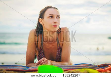 Girl lying on the beach and looking to the side tans lying on his stomach