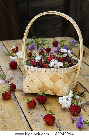 Bast basket with strawberries on a light wooden table with scattered berries and flowers