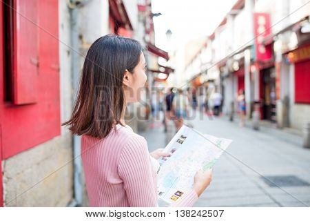 Woman looking at city map in Rua da Felicidade of Macao city
