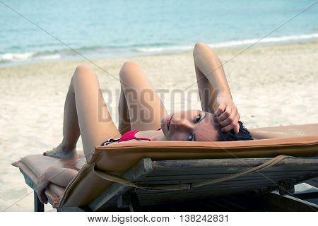The girl lies on a sun lounger and relax looks into the camera