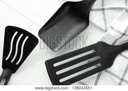 black ladle and spade of frying pan on the white table