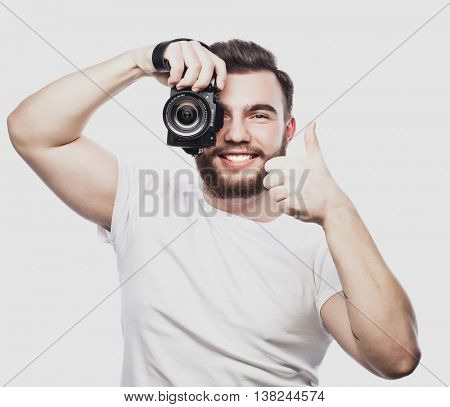 young bearded photographer taking pictures with digital camera.
