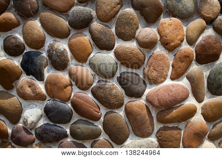 Gray and brown pebble mosaic wall textured background. Tiled stone decoration design backdrop