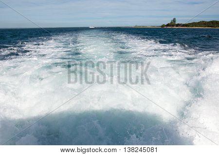Foamy boat wake trailing in the Indian Ocean waters in Rockingham, Western Australia.