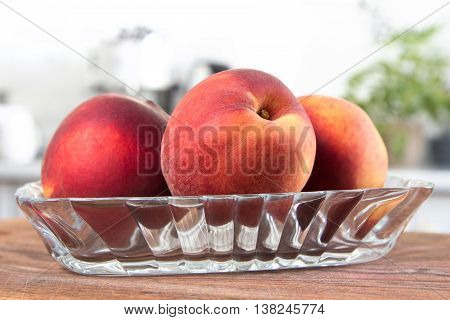 Few red and yellow peaches on glass pale. White modern kitchen at the background