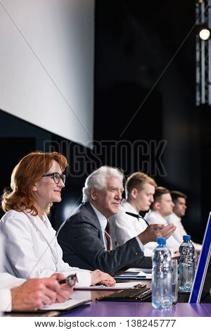 Smiling participants of a conference sitting behind a desk with laptops and bottles of water