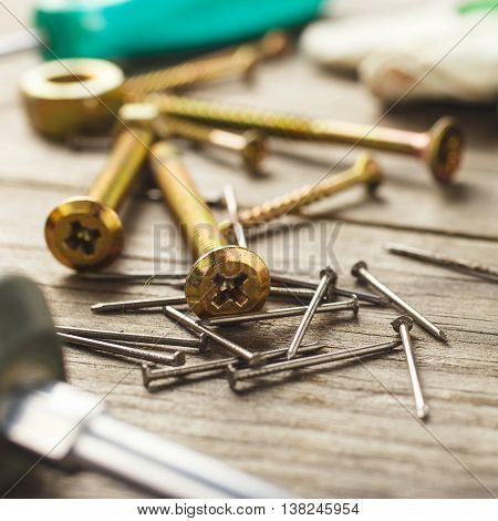 Cross head bolt screws thread with nails on wooden desk closeup
