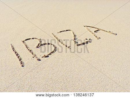 Ibiza drawing in the sand. Text on the beach.