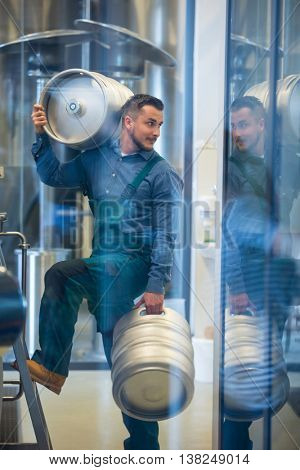 Brewer carrying keg at brewery