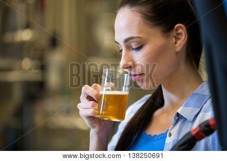 Close-up of beautiful female brewer testing beer at bewery